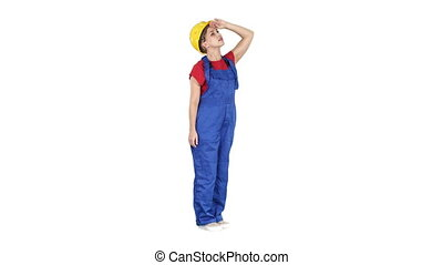 Engineer woman in yellow helmet looking up amazed at a building or statistics or graph on white background.