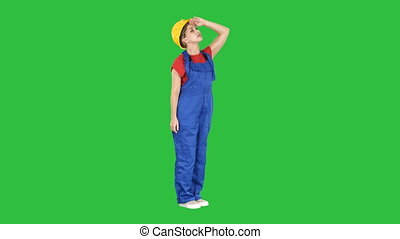 Engineer woman in yellow helmet looking up amazed at a building or statistics or graph on a Green Screen, Chroma Key.