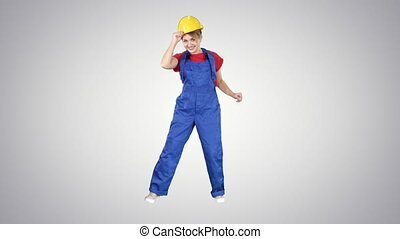Female construction worker funny dance on gradient background.