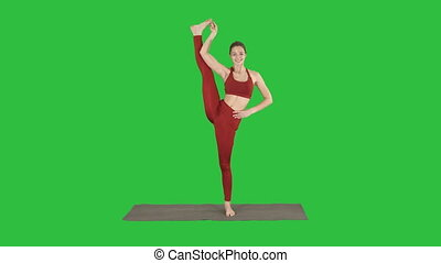 Female Yoga Model Making Standing Split Smiling on a Green...