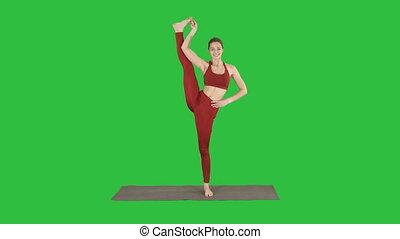 Female Yoga Model Making Standing Split Smiling on a Green...