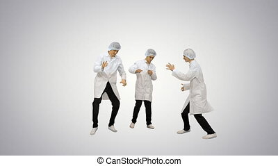 Full length shot. Front view. Three male doctors in white robes and protective caps doing funny celebration dance on gradient background. Professional shot in 4K resolution. 045. You can use it e.g. in your medical, commercial video, business, presentation, broadcast