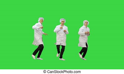 Full length shot. Front view. Three male doctors in white robes and protective caps doing synch dance routine looking at camera on a Green Screen, Chroma Key. Professional shot in 4K resolution. 045. You can use it e.g. in your medical, commercial video, business, presentation, broadcast
