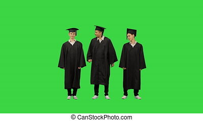 Full length shot. Front view. Three male students in graduation robes and mortar boards warming up while waiting on a Green Screen, Chroma Key. Professional shot in 4K resolution. 045. You can use it e.g. in your medical, commercial video, business, presentation, broadcast