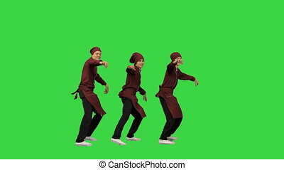 Full length shot. Front view. Three smiling chef cooks in red uniform synch dancing against green background and pointing at camera at the end on a Green Screen, Chroma Key. Professional shot in 4K resolution. 045. You can use it e.g. in your medical, commercial video, business, presentation, ...
