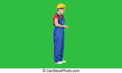 Happy young constructor counting her money on a Green Screen, Chroma Key.