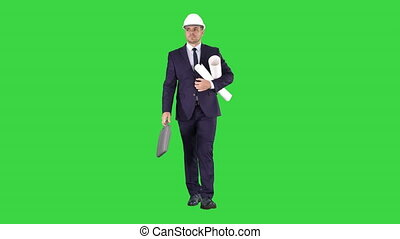 Male architect in a suit and hard hat walking with blueprints and briefcase on a Green Screen, Chroma Key.