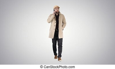 Man in trench coat walking and talking on the phone on...