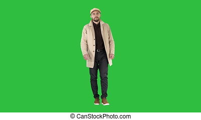 Man with dark beard in light trench coat walks on a Green Screen, Chroma Key.