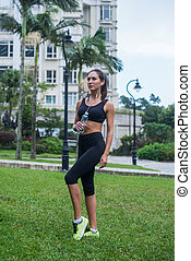 Full length shot of beautiful fitness female model in black sportswear standing on grass in city park and listening to music in earphones holding a bottle