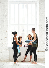 Full-length shot of positive people talking in gym -...
