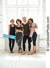 Full-length shot of positive people with training mats