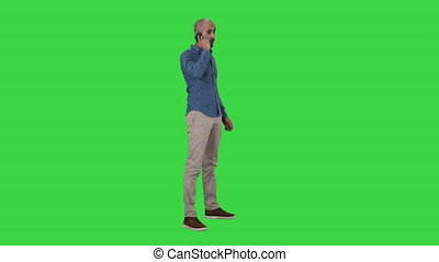 Serious arab talking on the phone on a Green Screen, Chroma Key.