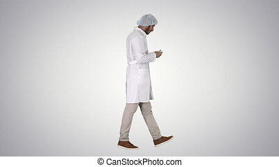 Arabic doctor walking and putting medical cap on on gradient...