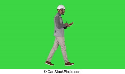 Arabic man in casual clothes and hard hat writing down...