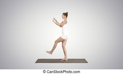 Beautiful young woman doing yoga exercise for ankles,...