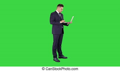 Businessman standing and using laptop on a Green Screen,...