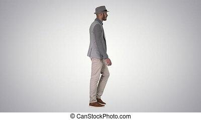 Casual arabic man in hat walking on gradient background. -...