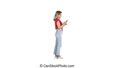 Casual young woman typing on mobile phone on white background.