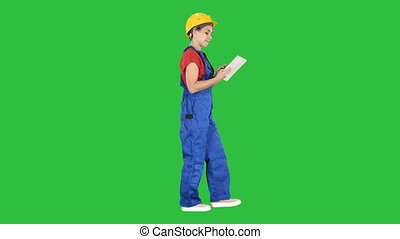 Construction lady using electronic tablet walking on a Green Screen, Chroma Key.