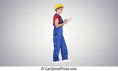 Construction lady using electronic tablet walking on gradient background.