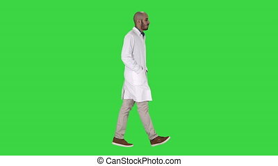 Doctor walking with hands in pockets on a Green Screen, Chroma Key.