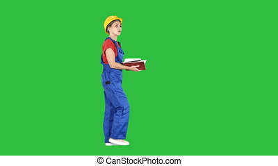 Female engineer in yellow safety helmet checking documentation with what is built on a Green Screen, Chroma Key.