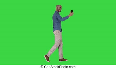 Happy smiling handsome young man making selfie while walking on a Green Screen, Chroma Key.