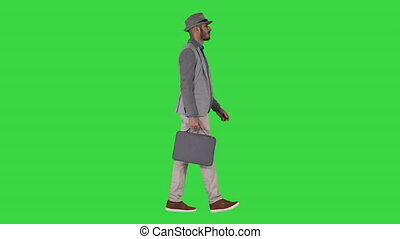 Man in casual walking with briefcase on a Green Screen,...