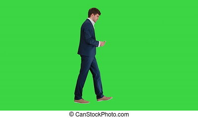 Full length shot. Side view. Satisfied businessman counting money and tucking it inside his jacket while walking on a Green Screen, Chroma Key. Professional shot in 4K resolution. 047. You can use it e.g. in your medical, commercial video, business, presentation, broadcast