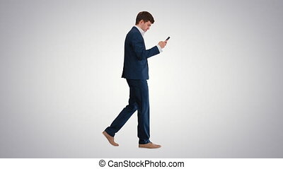 Full length shot. Side view. Serious businessman using phone voice dial while walking on gradient background. Professional shot in 4K resolution. 047. You can use it e.g. in your medical, commercial video, business, presentation, broadcast