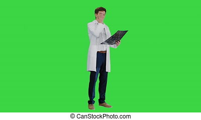 Full length shot. Side view. Shocked male doctor looking at computed tomography of the brain on a Green Screen, Chroma Key. Professional shot in 4K resolution. 047. You can use it e.g. in your medical, commercial video, business, presentation, broadcast