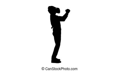 Full length shot. Side view. Silhouette Boy in formal wear playing the sword game in virtual reality goggles. Professional shot in 4K resolution. 060. You can use it e.g. in your medical, commercial video, business, presentation, broadcast