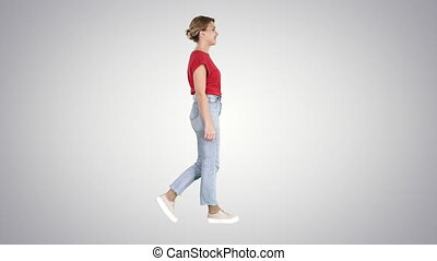 Woman in red t-shirt, jeans and sneakers walking on gradient...