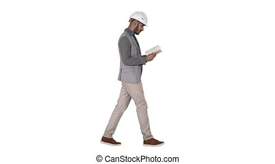 Young architect reading textbook or notebook while walking...