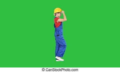 Young attractive woman in construction uniform putting on yellow helmet on a Green Screen, Chroma Key.