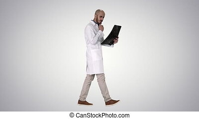 Full length shot. Side view. Young male physician reading and reviewing a MRI brain scan while walking on gradient background. Professional shot in 4K resolution. 011. You can use it e.g. in your commercial video, business, presentation, broadcast
