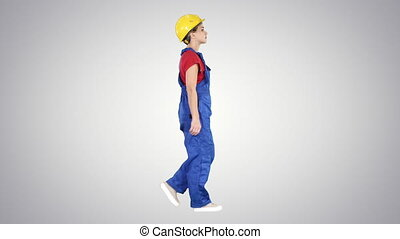 Young woman construction worker in yellow hardhat walking on...