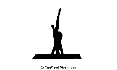 Silhouette Beautiful young woman doing yoga exercise variation of supported headstand, garuda salamba sirsasana with crossed legs.