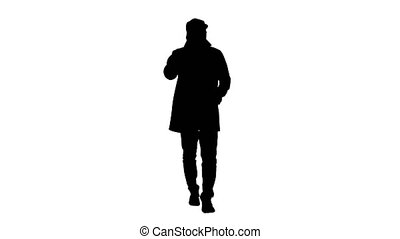 Silhouette Man in trench coat walking and talking on the...