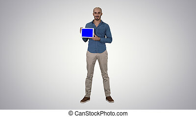 Smiling casual man presenting a tablet with a blank screen on gr