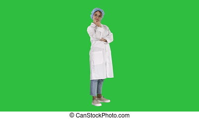 Smiling confident young woman doctor standing with arms crossed over on a Green Screen, Chroma Key.