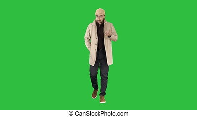 Talking young man in trench coat confidently talking to camera Just move forward on a Green Screen, Chroma Key.