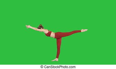 Tuladandasana or Balancing Stick Pose is an advanced yoga posture made by beautiful yogi woman on a Green Screen, Chroma Key.