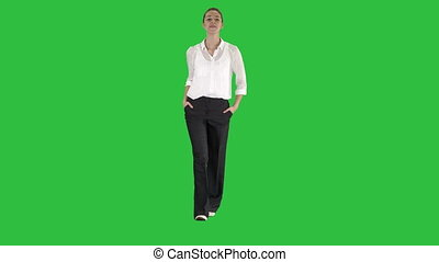 Walking businesswoman with hands in pockets and laughing on a Green Screen, Chroma Key.