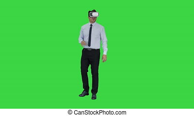 Astonished young businessman wearing VR glasses Concept of the future technology on a Green Screen, Chroma Key.