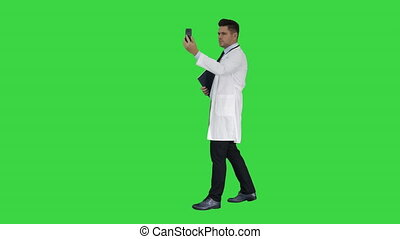 Male doctor making a video call talking to his patient on a Green Screen, Chroma Key.