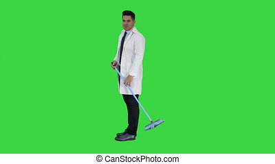 Man in white robe sweeping the floor and talking on a Green Screen, Chroma Key.