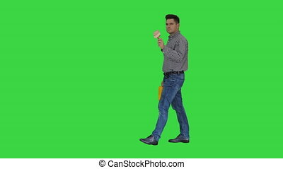 Painter man walking and pointing with brush on what he wants to paint on a Green Screen, Chroma Key.