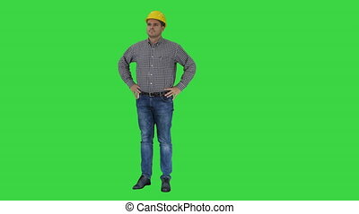 Smiling construction worker in yellow helmet looking at...